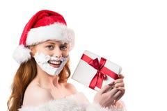 Festive redhead in foam beard holding gift Stock Photos