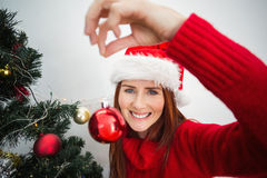 Festive redhead hanging bauble on tree Stock Photo