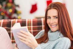 Festive redhead reading on the couch Royalty Free Stock Photos
