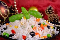 Festive rice salad. On the background of Christmas decorations Stock Photos