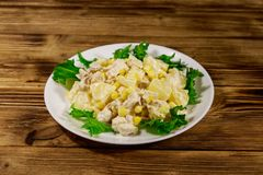 Festive salad with chicken breast, sweet corn, canned pineapple and mayonnaise on wooden table stock image