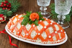 Festive salad, decorated with salmon on a wooden table imagen de archivo