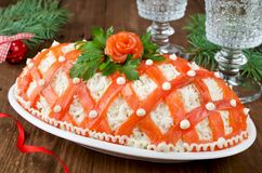 Festive salad, decorated with salmon on a wooden table fotografía de archivo