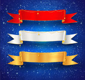 Festive satin ribbon banners. With gold garland decoration on blue grunge watercolor background with falling snow and light sparkles Royalty Free Stock Photography