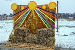 Festive scene with bales of straw and colorful ribbons. Decorations for Carnival at the village stadium Stock Photos