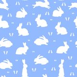 Festive Seamless Pattern, white bunnies silhouette on blue backg Stock Photography