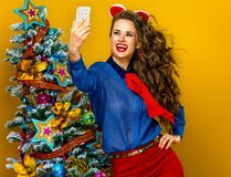 Woman near Christmas tree with digital camera taking selfie Stock Image