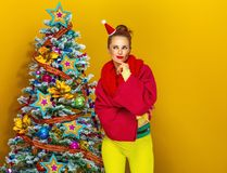 Woman near Christmas tree isolated on yellow background royalty free stock images