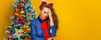 Stressed woman near Christmas tree  on yellow Stock Photos