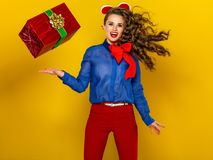 Woman  on yellow with red present box jumping Stock Photography