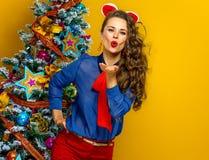 Smiling young woman near Christmas tree blowing air kiss. Festive season. smiling young woman near Christmas tree  on yellow background blowing air kiss Stock Photos