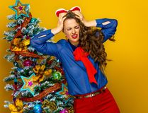 Stressed woman near Christmas tree  on yellow Royalty Free Stock Images