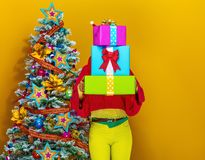 Woman holding pile of Christmas present boxes. Festive season. stylish woman in colorful clothes near Christmas tree isolated on yellow background holding pile Stock Image