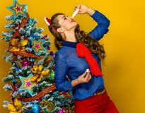 Trendy woman near Christmas tree using nasal spray Stock Image