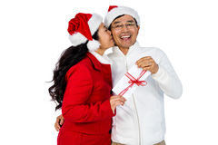 Festive senior couple exchanging gifts. On white background Stock Photos