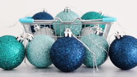 Christmas baubles in shopping basket with blue and silvery tones with focus changing from background to foreground ones stock video footage