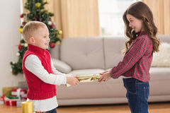 Festive siblings pulling a cracker Royalty Free Stock Photography