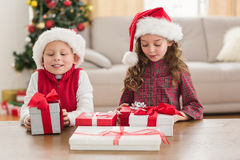 Festive siblings smiling at their gifts Stock Photo