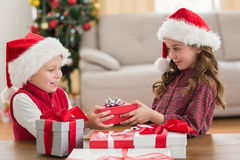 Festive siblings smiling at their gifts Royalty Free Stock Images
