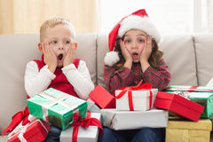 Festive siblings surrounded by gifts Royalty Free Stock Images