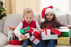Festive siblings surrounded by gifts Stock Photo