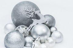Festive silver grey shiny Christmas ornaments with Santa's ninth reindeer at natural snow background Stock Photos