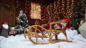 Festive sledges are among the Christmas trees. Parallax. Festive sledges are among the Christmas trees on the background of a wooden house decorated with stock video footage