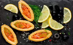 Festive snack salty salmon tartlet. On a black slate plate top view Stock Photography