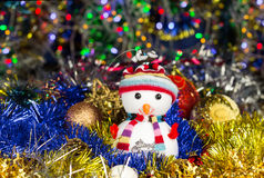 Festive snowman with Christmas balls, tinsel on blurred lights background Stock Photos