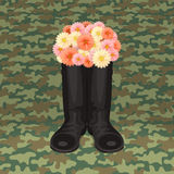Festive soldier's boots. Soldier's boots with bouquet of flowers, on green camouflage background Stock Image