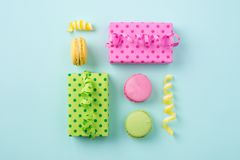 Festive flat lay with Gift boxes & colorful macarons on light bl. Festive square composition with bright gift boxes, confetti & colorful macarons on light blue Stock Images