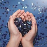 Festive star confetti heart shaped in hands stock photos
