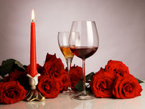 Festive still life. Still life with red roses, glasses and a candle Stock Photography