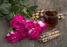 Festive still life from flowers, cookies and tea on a wooden table Royalty Free Stock Images