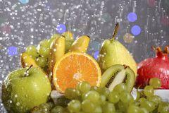 Festive still-life from fresh colorful fruits in drops and splashes of falling water . Stock Image
