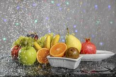 Festive still-life from fresh colorful fruits in drops and splashes of falling water . Royalty Free Stock Image