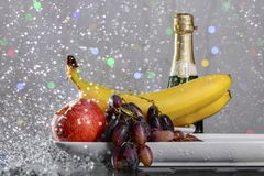 Festive still-life from fresh colorful fruits in drops and splashes of falling water . Royalty Free Stock Photography
