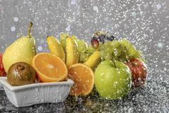 Festive still-life from fresh colorful fruits in drops and splashes of falling water . Stock Photos
