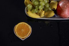 Festive still life of fresh multicolored fruits on a black background. Stock Photo