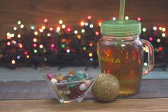 A festive still life with a glass clear cup of tea with a cap, a bowl of candies,a golden ball, fairy lights royalty free stock photos