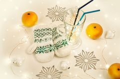 Festive still life. Knitted white mittens in the center. Mulled wine glass with magic lights in it. Silver snowflakes, white hearts and tangerines around Royalty Free Stock Photos