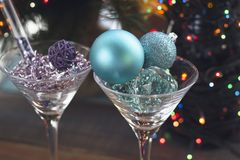 Festive still life with two cocktail glasses. Festive still life with Festive still life with two cocktail glasses with shiny blue and lilac Christmas-tree Stock Images