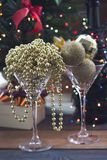Festive still life with two cocktail glasses. Festive still life with Festive still life with two cocktail glasses with shiny gold beads and Christmas-tree balls Royalty Free Stock Photos