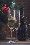 Festive still life with two glasses and a bottle of champagne. Festive still life with two glasses of champagne and a bottle wrapped up in garland. A Christmas Royalty Free Stock Images