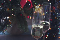 Festive still life with two glasses and a bottle of champagne. Festive still life with two glasses of champagne and an unfocused bottle wrapped up in garland. A Stock Photos