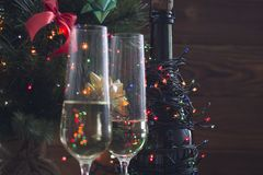 Festive still life with two glasses and a bottle of champagne. Festive still life with two glasses of champagne and a bottle wrapped up in garland. A Christmas Stock Image