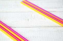 Festive summer concept with colorful drinking straw.s. Birthday invitation card, pink and yellow colors. nwhite wooden background and copy space Royalty Free Stock Photo