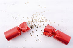 Festive surprise concept. Festive surprise concept with opened red bon bon Christmas cracker and glitter stars on white wood table with copy space for your text Stock Photography