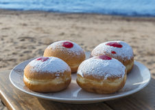 Festive sweet donuts with jam at sandy beach of the Red Sea Royalty Free Stock Images