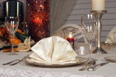 Festive Table. A dinning room table set for a holiday dinner. Focus on napkin royalty free stock image